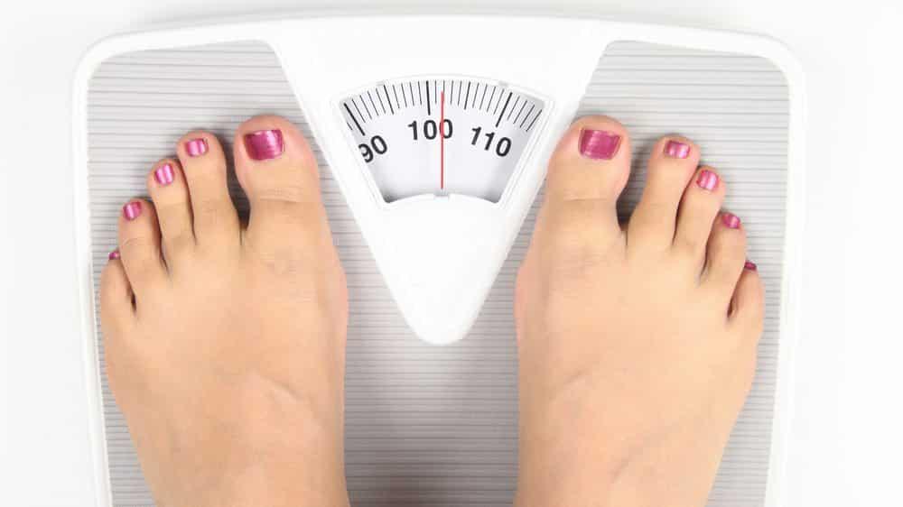 pés de mulher sobre a balança. Pesquisa mostra aumento da obesidade no Brasil
