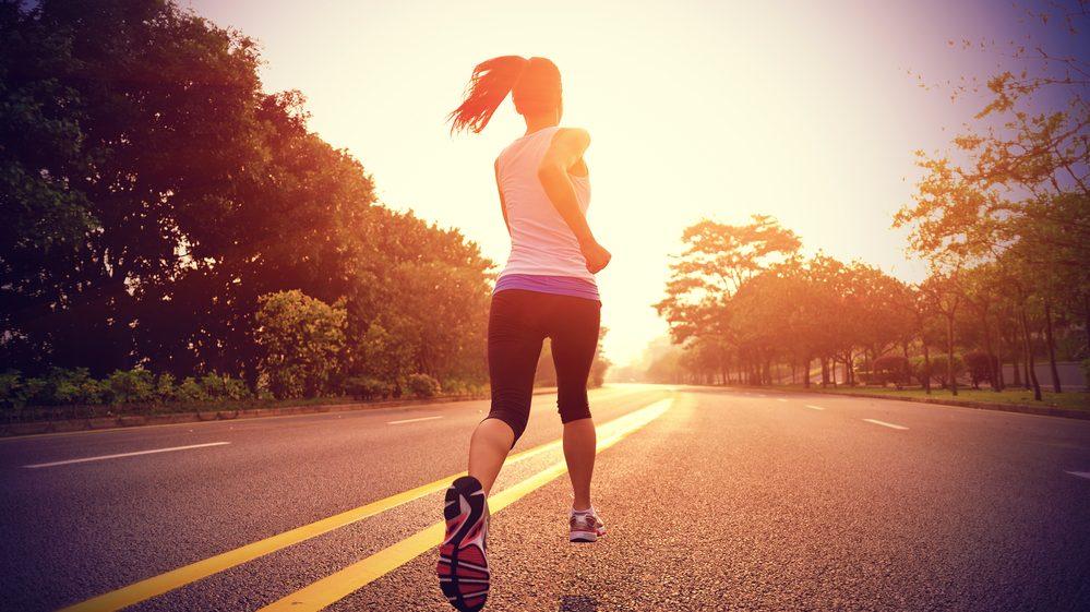 mulher corre com por do sol ao fundo.Exercícios físicos e alimentação balanceada são essenciais para um emagrecimento saudável
