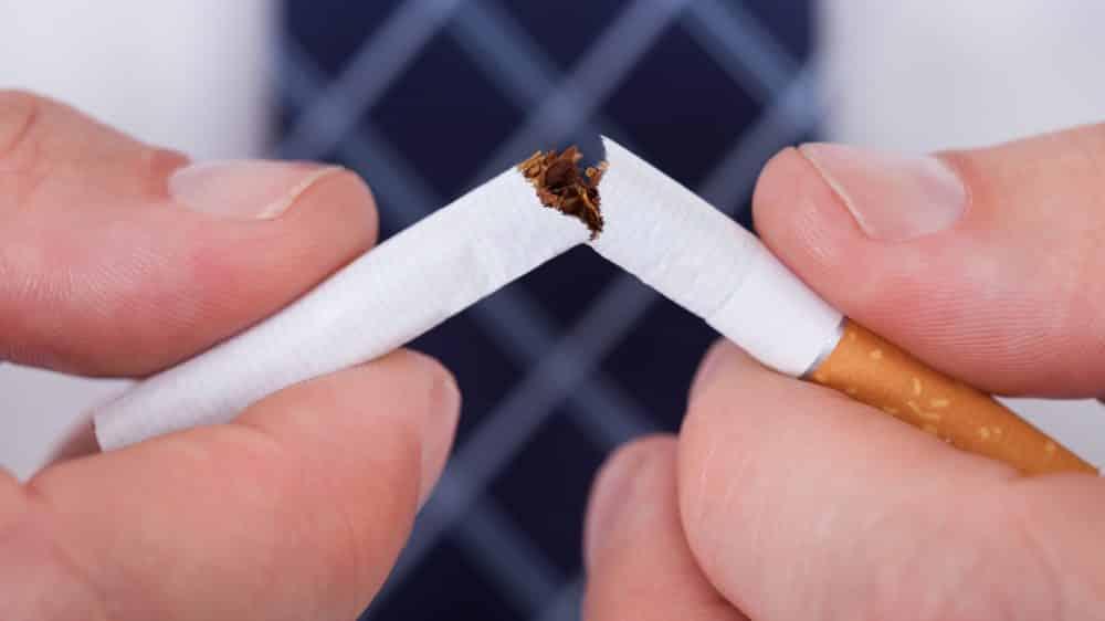 mãos de homem quebrando um cigarro ao meio. custos do cigarro são altos