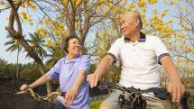 casal de idosos anda de bicicleta em parque. Prevenção das demências inclui exercício fisico