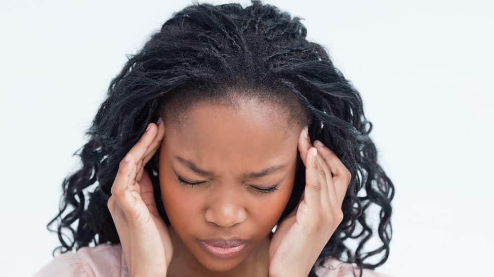 Mulher com as mãos na cabeça em sinal de dor.