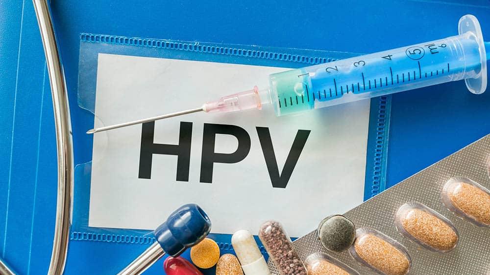 Etiqueta com HPV escrito e seringa e comprimidos sobre ela.