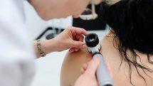 Médica examinando pele da região do ombro de uma paciente.