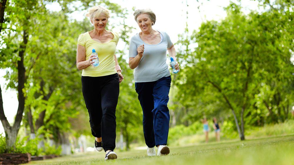 duas mulheres mais velhas praticam corrida; relação entre atividade física ajuda na prevenção ao câncer