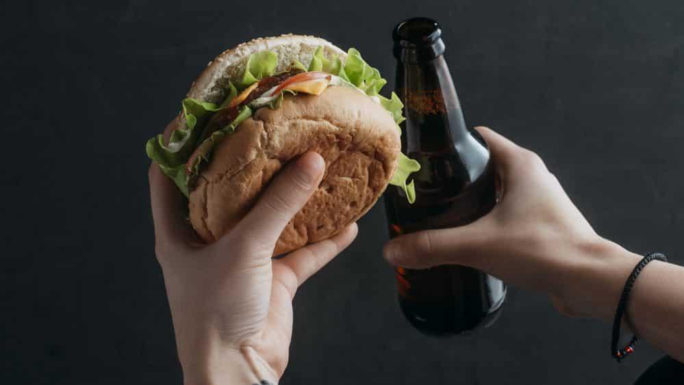 homem segura hambúrguer e cerveja, mostrando estilo de vida prejudicial à saúde