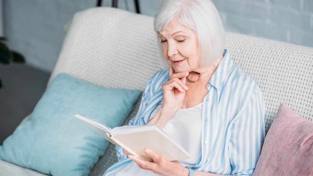 idosa lê no sofá. veja a relação entre demência e intelectualidade