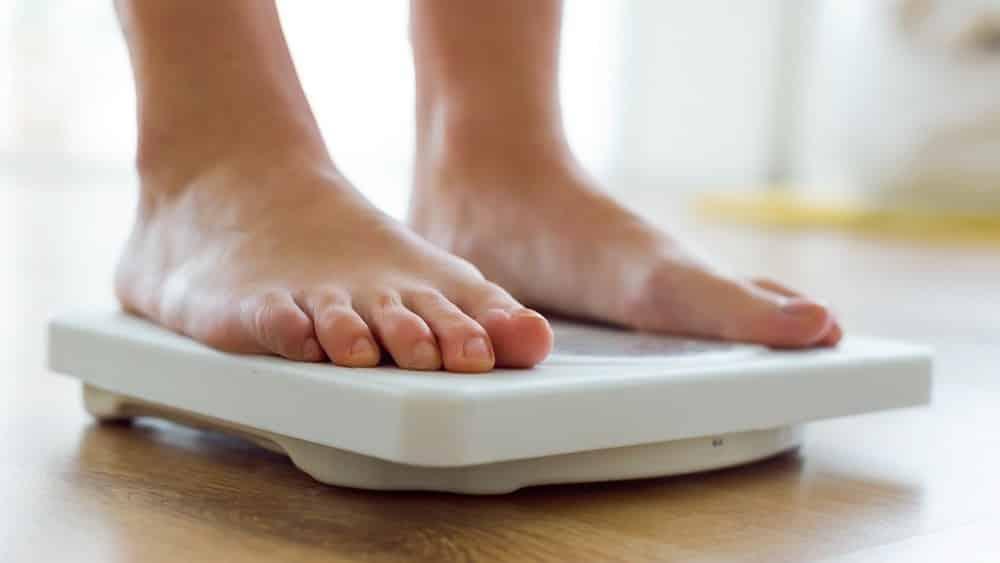 mulher se pesando em balança. o paradoxo da obesidade mostra