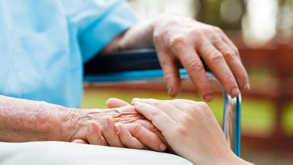 idoso sentando, de mãos dadas com jovem. Suicídio assistido ainda é tabu