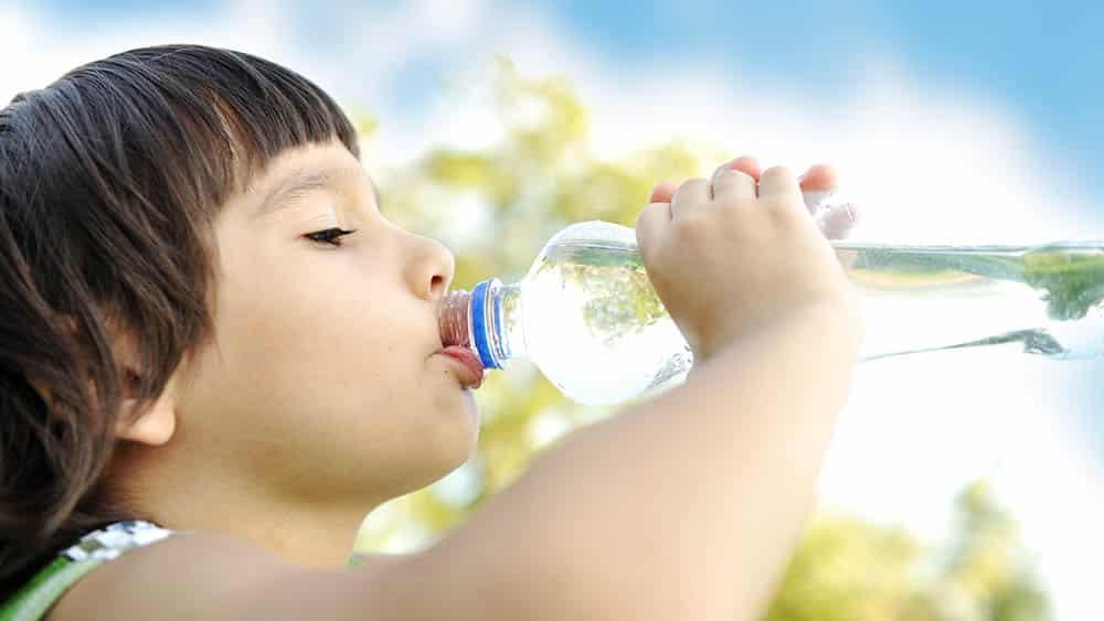 Imagem de criança bebendo água de uma garrafa.