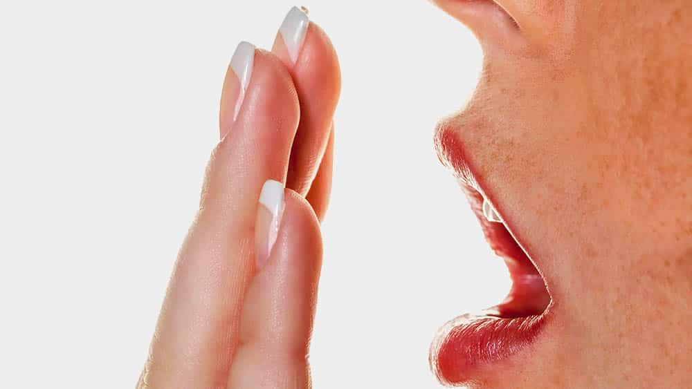 Pessoa com a mão sobre a boca indicando mau hálito.