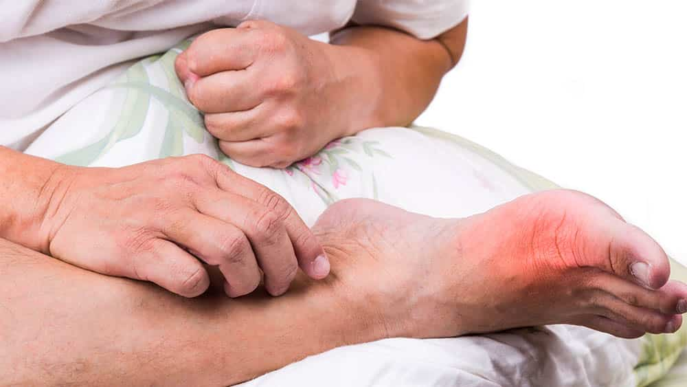 Homem com perna cruzada e destaque vermelho próximo do dedão do pé indicando inflamação.