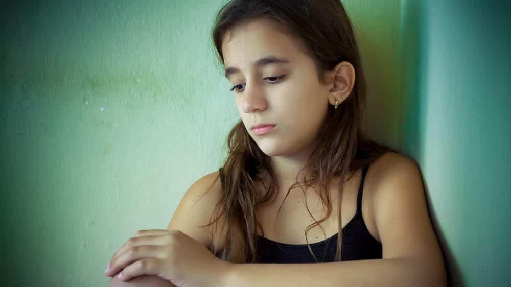 menina triste, sentada encostada na parede. Trump criou política para tornar crianças ilegais