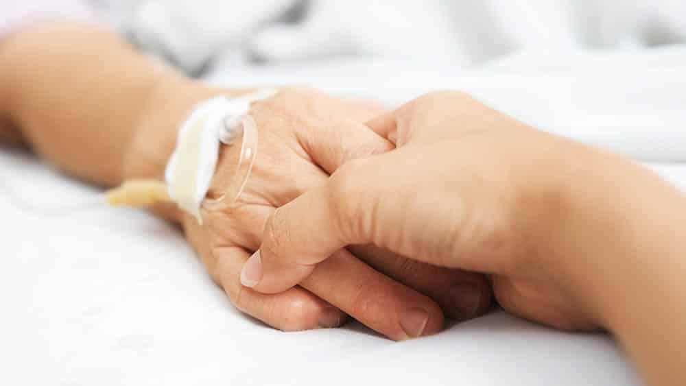 Close em uma mão segurando a mão de idosa acamada.