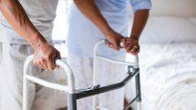 Homem apoiado em um andador sendo ajudado por um profissional de reabilitação.