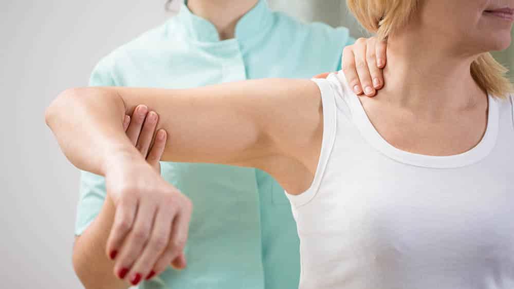Mulher erguendo braço de uma paciente em sessão de fisioterapia.