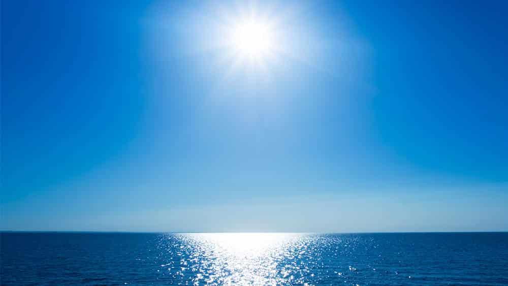 Imagem de horizonte com sol forte e linha do mar.