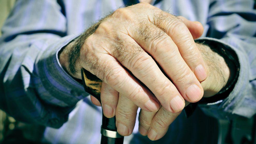 mãos de homem idoso apoiadas em bengala. A expectativa de vida dos americanos caiu