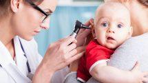 Bebê tem seu ouvido examinado por médica enquanto está no colo da mãe.