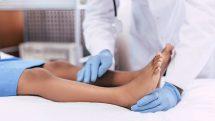 Pernas de criança deitada sendo examinadas por médico.