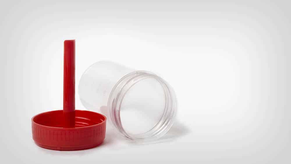 Pote usado em coleta de amostra de fezes em um fundo branco.