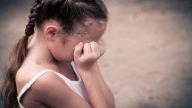 Menina com as mãos no rosto escondendo choro. Mudança de comportamento pode ser sinal de violência contra crianças
