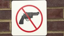 Cartaz colado em um muro, com desenho indicando que armas não são permitidas.