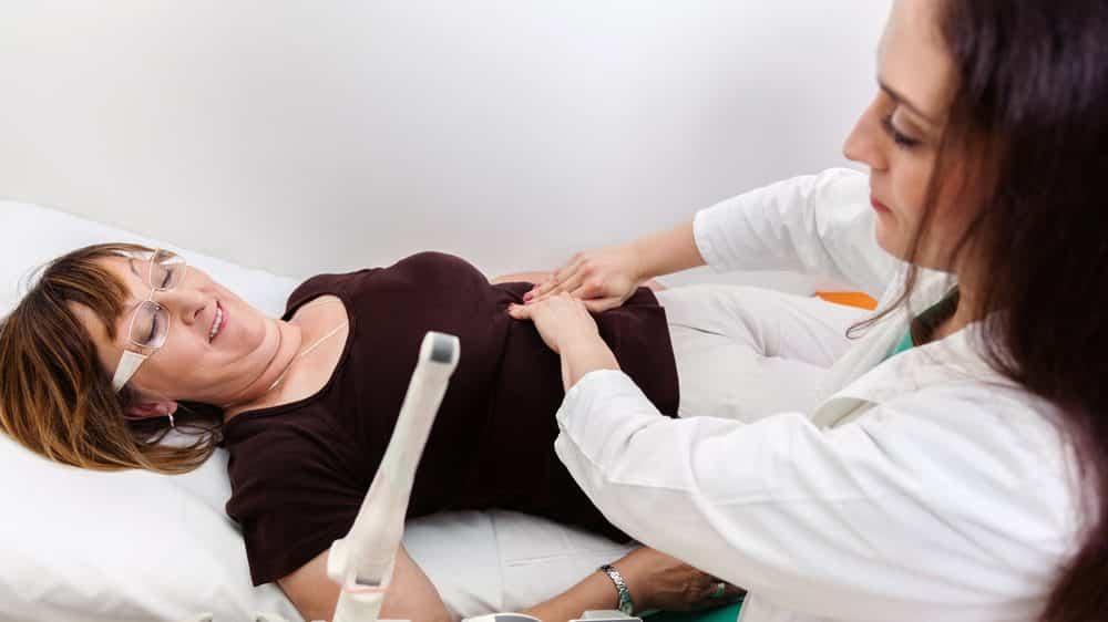 mulher na menopausa deitada em cama é examinada por médica ginecologista