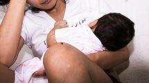 Menina adolescente com bebê mamando e uma mão na cabeça indicando preocupação.