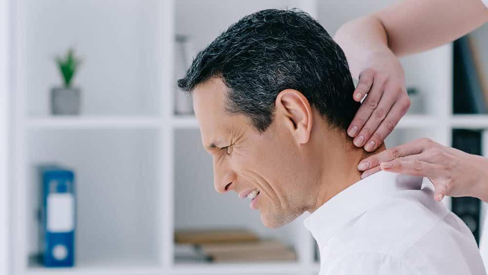 Homem de perfil com expressão de dor de torcicolo enquanto a região cervical é massageada.