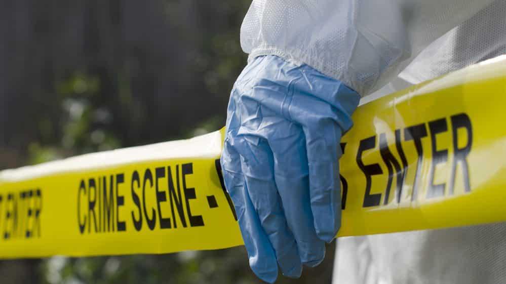 Mão com luva sobre uma faixa amarela típica de isolamento de cenas de crime.