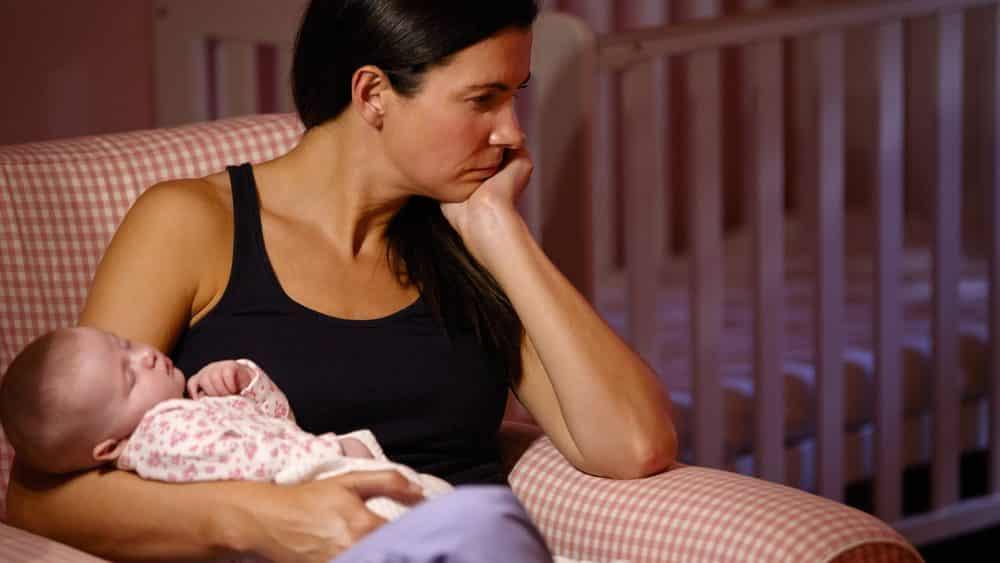 mãe sofrendo de depressão perinatal segura bebê dormindo no colo
