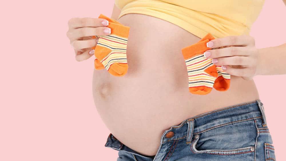 Mulher grávida segurando dois pares de meia ao lado barriga. Gravidez de múltiplos deve ser acompanhada