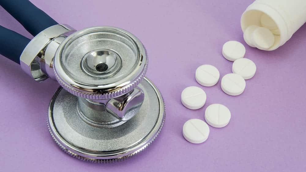 Estetoscópio e, ao lado, medicamentos para hipertensão caindo fora de pote sobre a superfície.