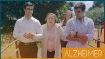 Dona Marisa, paciente com Alzheimer, caminha auxiliada por cuidadores.