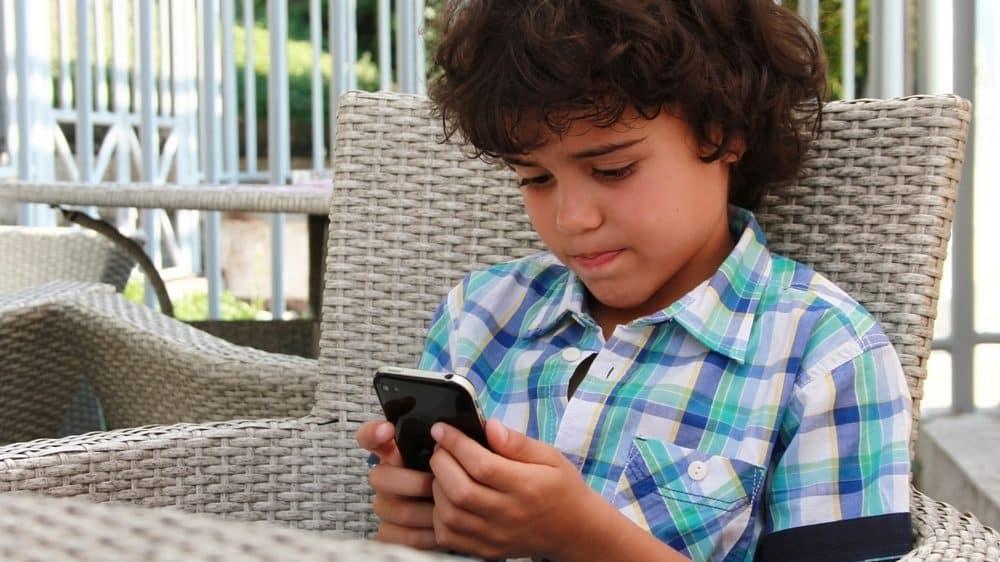 menino acessa o celular. OMS lança diretrizes para uso de aparelhos digitais