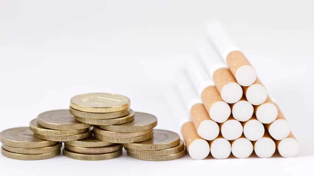 moedas e pilha de cigarros. reduzir impostos sobre o cigarro vai contra recomendação da OMS