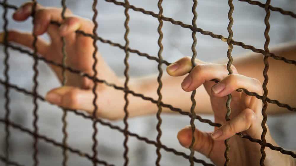 mão de mulher presa apoiada na grade. Mulheres presas em geral são abandonadas pela família