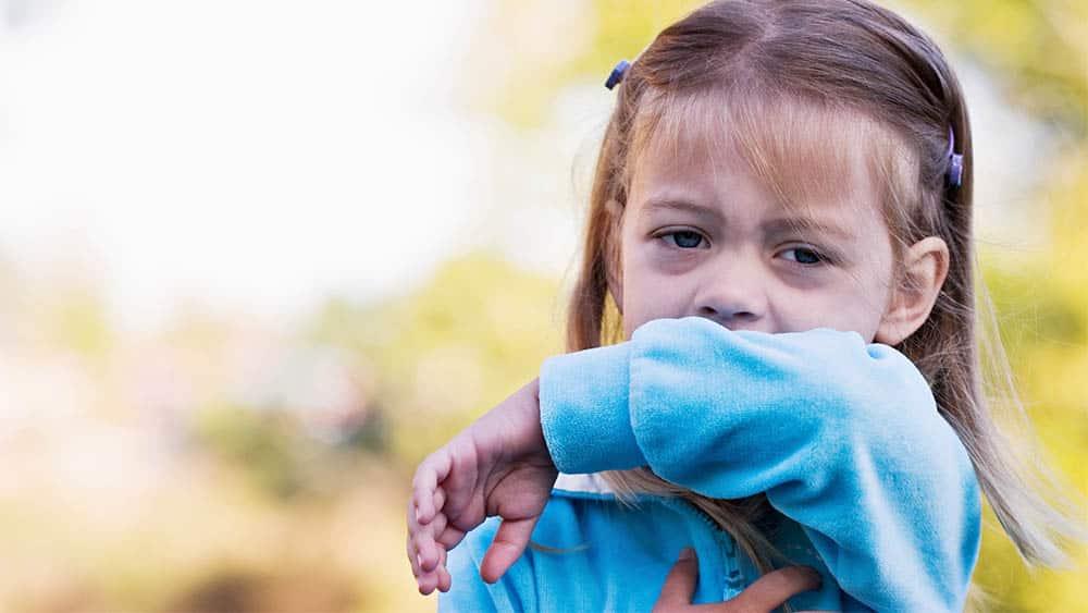 Menina com olhos de coriza limpando a boca com o braço.
