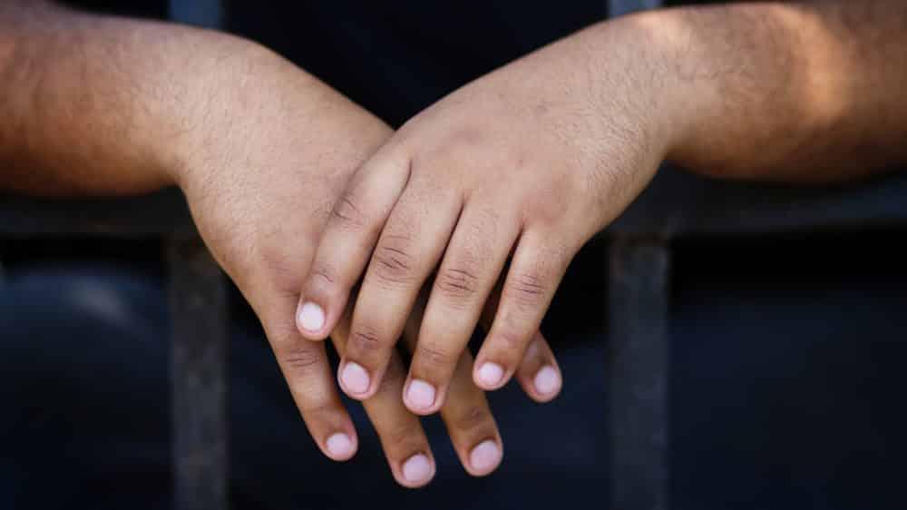 Mãos de rapaz preso atrás de grades.