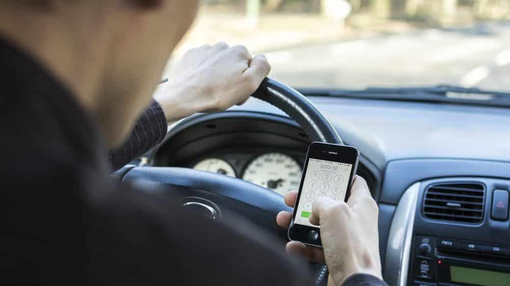Homem dirige enquanto checa o celular.