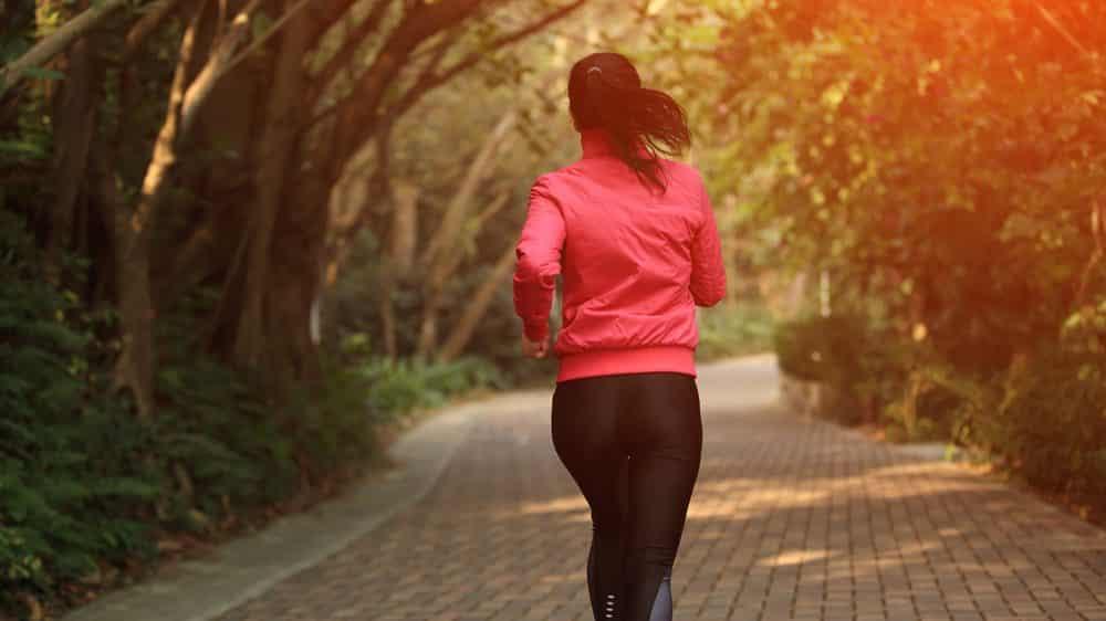 mulher correndo em trilha arborizada. atividade física ajuda no controle de doenças