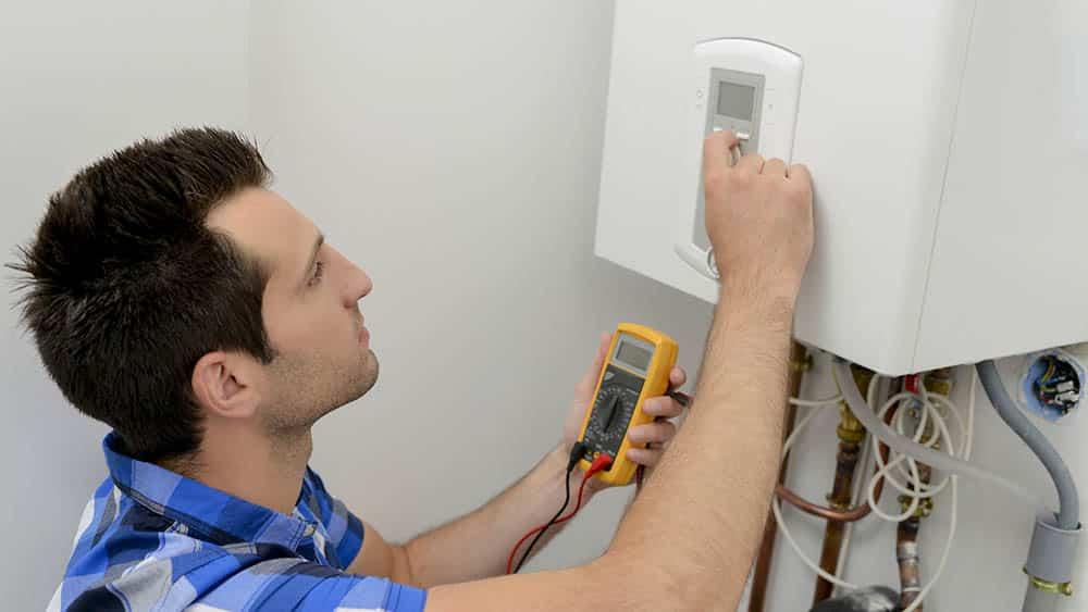 Homem fazendo manutenção em aquecedor a gás.
