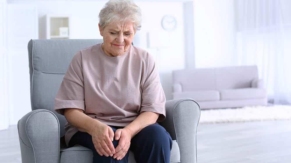 Idosa sentada no sofá segurando joelho com expressão de dor. Reumatismo não piora no firo