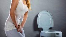 Mulher pressionando a região genital indicando infecção urinária com vaso sanitário ao fundo.