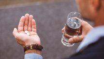 Executivo com um copo de água em uma mão e dois comprimidos brancos em outra prestes a ingeri-los.