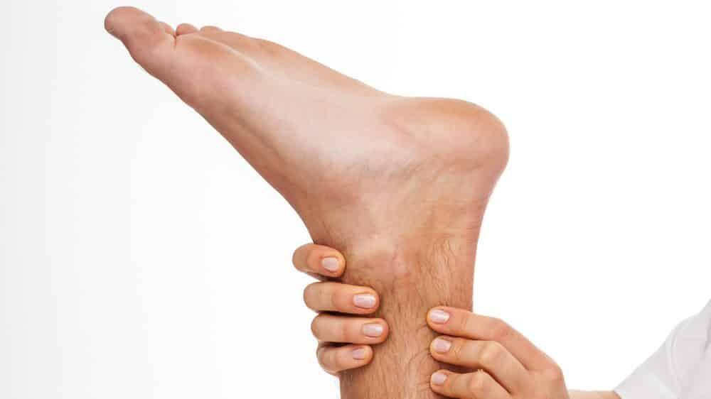 close de fisioterapeuta palpando o tendão de Aquiles de paciente