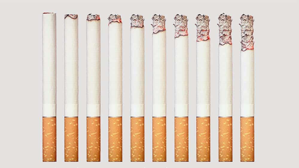 Cigarros lado a lado cada um com a ponta mais queimada que o anterior.