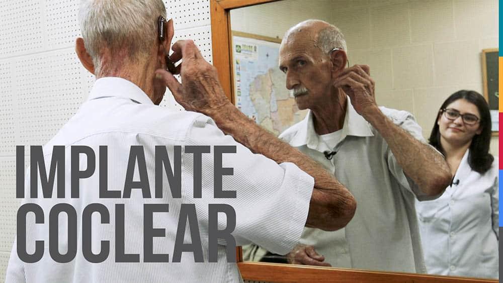 Paciente colocando aparelho de implante coclear em frente ao espelho.