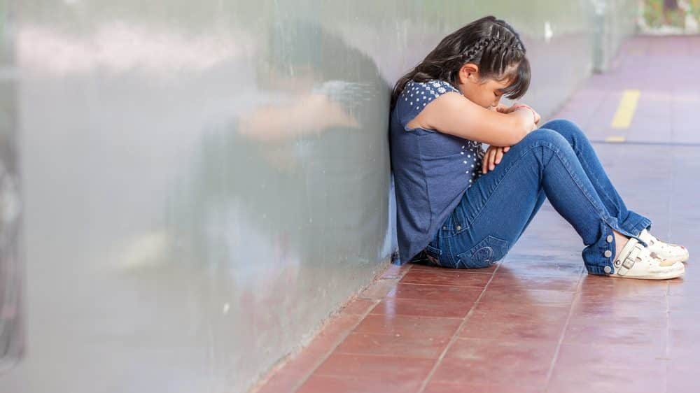 menina triste sentada no chão sozinha. Maioria das vítimas de estupro são crianças e adolescentes.