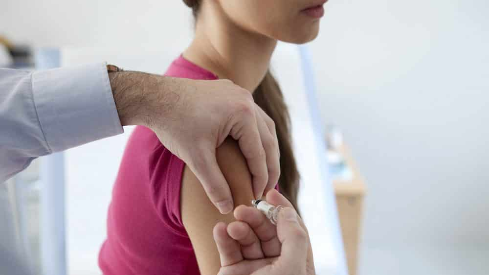 mulher jovem toma vacina contra o sarampo